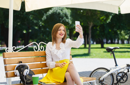narcissistic: Teen student girl or young woman in yellow skirt and white blouse uses tablet pc making selfie on the bench near a folding bicycle in the park Stock Photo
