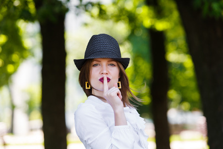 silence: Young beautiful sexy woman in stylish straw fedora hat showing hush sign with finger at her red lips, making silence gesture - secret, mystery, adultery concept Stock Photo