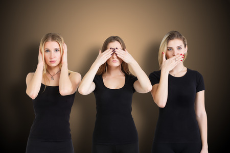 speaking: Three young woman in black clothes isolated at brown background showing blind, deaf and dumb: wise monkey scene - hear no evil, see no evil, speak no evil