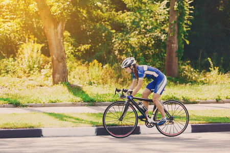 bicycle helmet: Female sportsman cyclist riding racing bicycle. Woman cycling on countryside summer sunny road or highway. Training for triathlon or cycling competition. Stock Photo