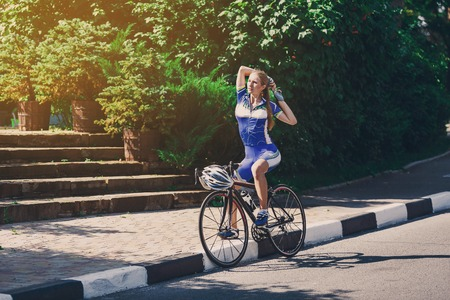 woman stretching: Female sportsman cyclist making stretching at bicycle. Woman cycling on countryside summer sunny road or highway. Training for triathlon or cycling competition.