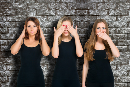 wise woman: Three young woman in black clothes isolated at grey brick wall background showing blind, deaf and dumb: wise monkey scene - hear no evil, see no evil, speak no evil