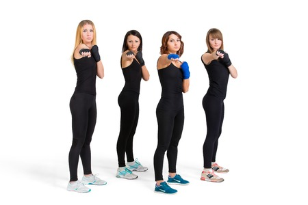 Fitness training studio shot - four young slim women in black sportswear making tae bo exercises isolated at white background