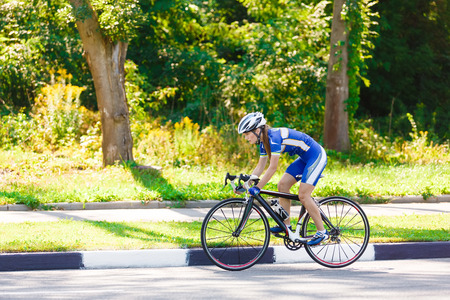 Female sportsman cyclist riding racing bicycle. Woman cycling on countryside summer sunny road or highway. Training for triathlon or cycling competition. Фото со стока