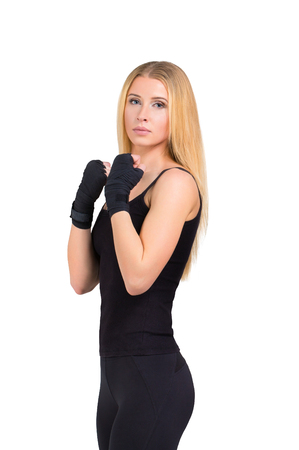 slim body: Fitness sporty woman studio shot - blonde girl stands in black sportswear showing tae bo exercise isolated at white background Stock Photo