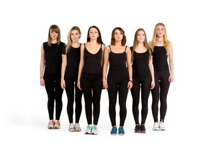 sameness: Group of young slim sporty women, blondes and brunettes, girls, friends, standing still in a line, row, sport team, in black fitness clothing, sportswear, teamwork concept. Stock Photo