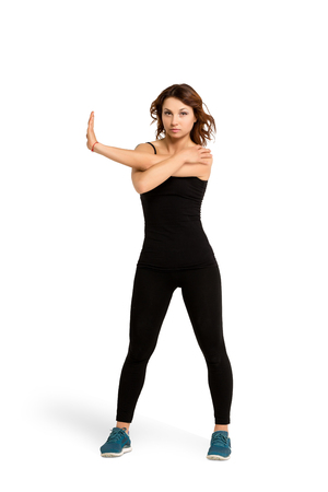 Young slim sporty athletic woman in black sportswear doing yoga stretching and warm-up before fitness training, isolated at white Stock Photo
