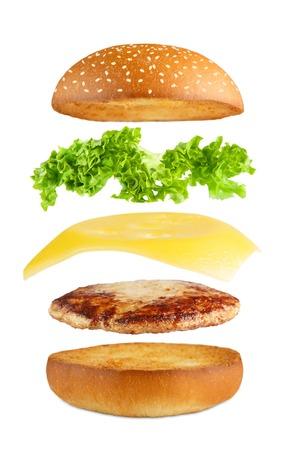 Amerikaans eten. Burger lagen geïsoleerd. Gescheiden hamburger lagen geïsoleerd. Hamburger exposion. Cheeseburger vliegen vullingen die bij witte achtergrond. Levitatie van hamburger en kaas, vlees, sla.