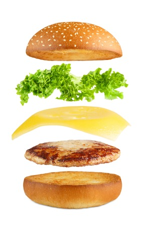 American food. Burger layers isolated. Separated burger layers isolated. Hamburger exposion. Cheeseburger flying fillings isolated at white background. Levitation of burger and cheese, meat, lettuce.