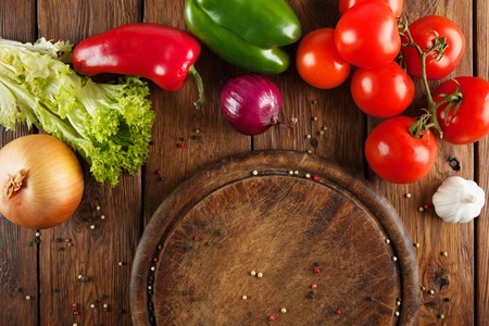 ingridients: Various vegetables at wooden rustic background with copyspace on round pizza desk. Set of fresh vegetables. Vegetables top view, tomatoes, pepper, lettuce, onion, garlic, red onion. Pizza ingridients.