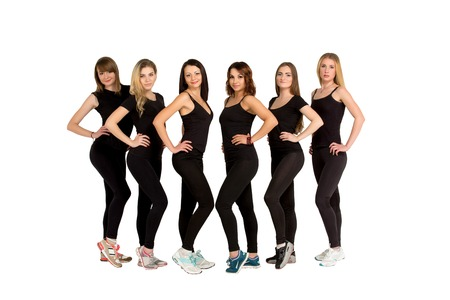 sameness: Group of young slim sporty women, blondes and brunettes, girls, friends, standing still in a line, row, sport team, in black fitness clothing, sportswear, teamwork concept. Fitness women group.