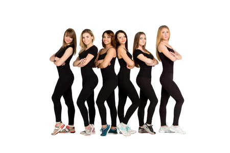 sameness: Group of young slim  sporty women, blondes and brunettes, girls, friends, standing still in a line, row, sport team, in black fitness clothing, sportswear, teamwork concept. Fitness women group. Stock Photo