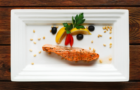 fish dish: Restaurant food, salmon dish. Hot fish dish. Barbecue grilled fish dish. Restaurant food catering. Salmon barbecue grill roasted with lemon and olives. Grilled salmon served in restaurant closeup.