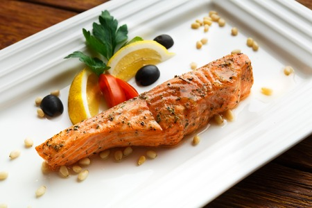 dish fish: Restaurant food, salmon dish. Hot fish dish. Barbecue grilled fish dish. Restaurant food catering. Salmon barbecue grill roasted with lemon and olives. Grilled salmon served in restaurant closeup.