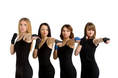 tae: Fitness training studio shot - four young slim women in black sportswear making tae bo exercises isolated at white background. Fitness woman group. Stock Photo