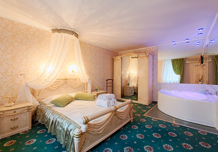 Vintage classic hotel bedroom interior. Bedroom interior design. Vintage luxurious bedroom premium suite with bath. Hotel classic interior. Double bed with canopy and golden drape, white towels.