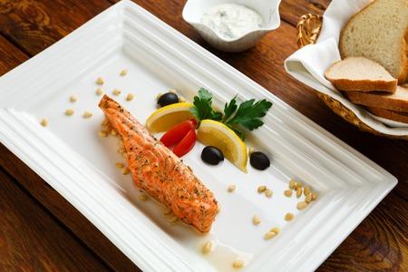 plato de pescado: La comida del restaurante, plato de salmón. Plato caliente de pescado. Barbacoa parrilla plato de pescado. La restauración de alimentos restaurante. Salmón asado parrilla con limón y aceitunas. salmón a la parrilla servido en el restaurante del primer.