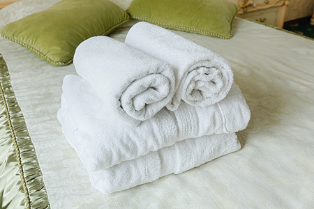 white towels: Towels in Hotel room. Closeup of hotel bedroom towels, selective focus. Welcome guests. Room service. White hotel towels rolled up at bed. Stock Photo