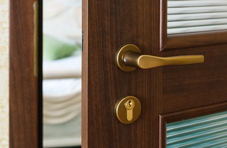 Half opened door of a bedroom. Hotel bedroom door half open. Hotel room welcome guests. Opening door closeup. Door handle. Privacy, intimacy concept. Entrance to the hotel bedroom.