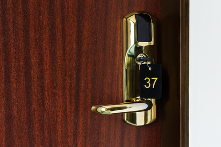 hotel room door: Half opened door of a room with number 37 on it. Hotel room door with lock half open. Hotel suit welcome guests. Opening door closeup. Door handle. Privacy concept. Entrance to the hotel room.