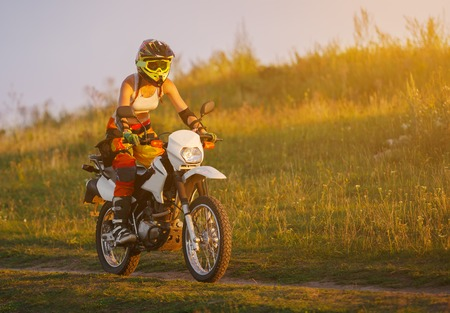 girl bike: Woman biker rides in fields. Sporty woman biker at motobike. Countryside, country road.  sunset, female motorcycle rider, motorbike rider traveling the world, girl resting, freedom lifestyle