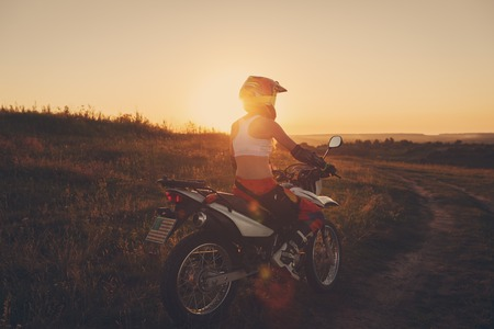 girl bike: Woman biker rides in fields. Sporty woman biker at motobike. Countryside, country road.  sunset, female motorcycle rider, motorbike rider travel the world, girl resting, freedom lifestyle, back view