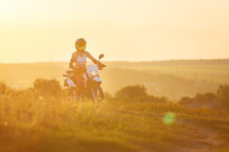 biker: Woman biker rides in fields.