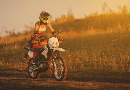Woman biker rides in fields.