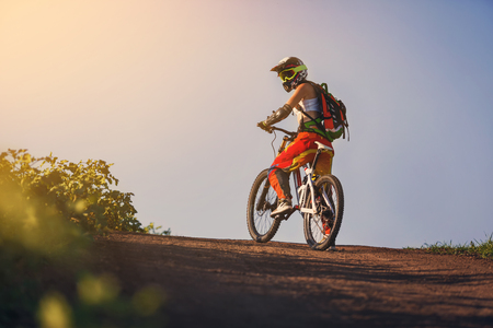 Extreme summer sports - young sportive strong woman or sportswoman riding downhill on mountain bicycle in helmet and other protective gear