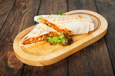 snack food: Mexican restaurant fast food - wrapped burritos with chili con carne closeup at wooden desk on table