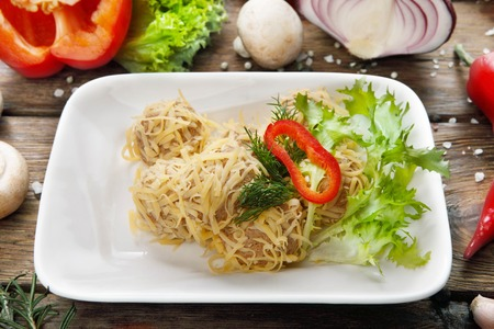 cooked pepper ball: Meat pate balls served with lettuce and cheese. Served at wooden rustic background with vegetables.