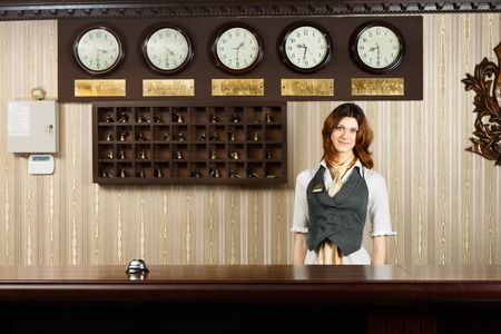 concept hotel: Hotel reception. Female receptionist at reception. Modern hotel reception counter desk with bell. Woman receptionist, concierge at desk. Travel, hospitality, hotel booking concept.