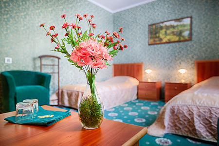 double rooms: Bouquet of flowers on the table in hotel room. Selective focus on flower bouquet