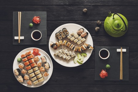 Sushi at rustic wood background and black stone. Top view at black.