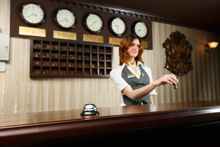 reception counter: Modern hotel reception counter desk with bell. Hotel receptionist gives keys to a guest. Stock Photo