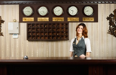 reception counter: Hotel reception. Female receptionist at reception. Modern hotel reception counter desk with bell.