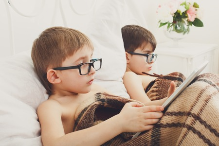 poor eyesight: Two children, boys in parents bed at morning with laptop and tablet.