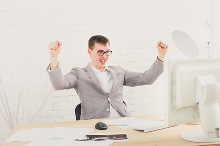 achievment: Winner businessman happy, succesful, in white modern office interior, sitting at computer table.