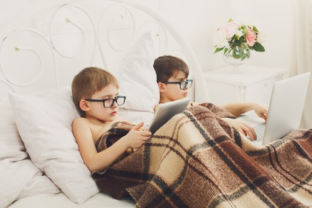 poor eyesight: Two children, boys in parents bed at morning with laptop and tablet. Brothers play computer games.