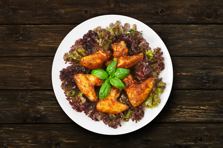 american cuisine: American cuisine, restaurant food -  fried roasted chicken wings on lettuce with basil at round white plate at wooden rustic background. Top view, flat lay