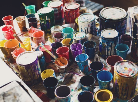oilpaint: Multicolored plastic cans with paints. Artist workplace background. Old dirty Paints background.