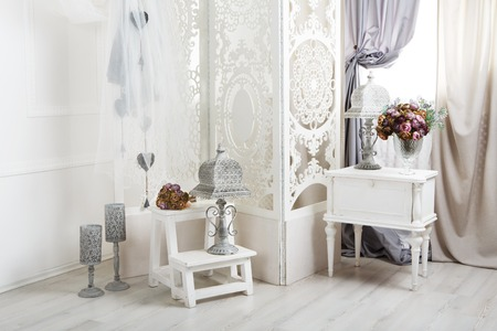 Wedding decor, room decorated for shabby chic rustic wedding, with bedside table, folding screen or room divider with white tracery and rose bouquets. 写真素材