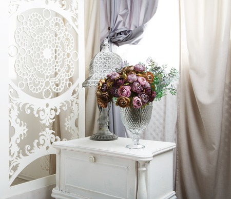 Wedding decor, room decorated for shabby chic rustic wedding, with bedside table, folding screen or room divider with white tracery and rose bouquets. Stock Photo