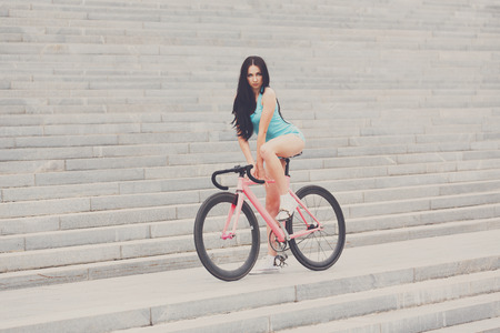 snickers: Young slim sexy sportive woman in blue shorts and white snickers long-haired, sensual posing on pink fix bicycle at grey stairs background. Stock Photo