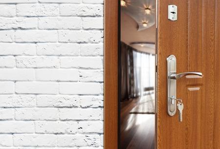 room door: Half opened door to a living room. Door handle, door lock. Lounge door half open. Opening door. Welcome, privacy concept. Entrance to the room. Door at white brick wall, modern interior design.