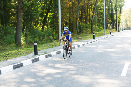 Female sportsman cyclist riding racing bicycle.