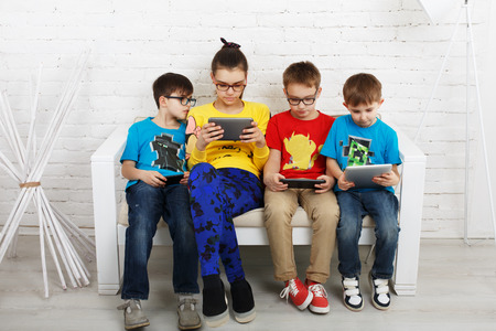 poor eyesight: Group of kids in eye glasses look into their phones and tablets. Stock Photo