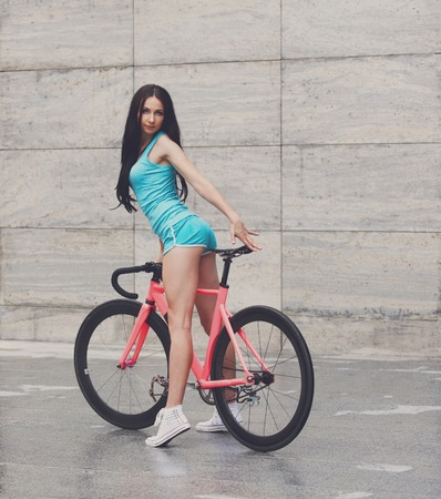 sensual girl: Young slim sexy sportive woman in blue shorts and white snickers long-haired, sensual posing with pink fix bicycle in urban city environment.
