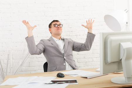 achievment: emotional businessman in white modern office interior, sitting at computer table.