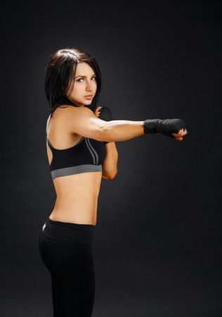 tae: Young sportive woman shows good fitness shape. Sporty strong body, girl in fitness wear shows fist, tae bo fitness. Slim brunette at black background, studio portrait. Female fighter. Stock Photo